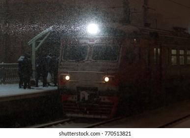 SAINT-PETERSBURG, RUSSIA - DECEMBER 06, 2017: Passengers board on the evening suburban train in heavy snowfall.
