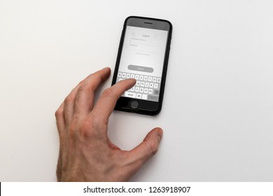 Saint-Petersburg / Russia - December 18 2018: Hand touching phone with Log In page, it is asking to enter username or email and password