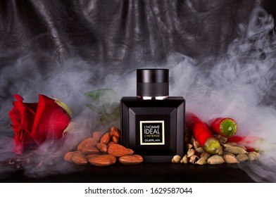 Saint-Petersburg, Russia - December  28, 2019: Bottle of perfume Guerlain - L`homme Ideal L`intense with red rose, almond nuts, spices and smoke on a black leather background.