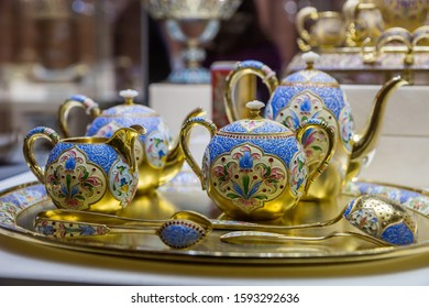 SAINT-PETERSBURG, RUSSIA - DECEMBER 3, 2018: Tea set of gilded vintage tableware with enamel decor. Exgibition of the Faberge Museum in Shuvalov Palace.