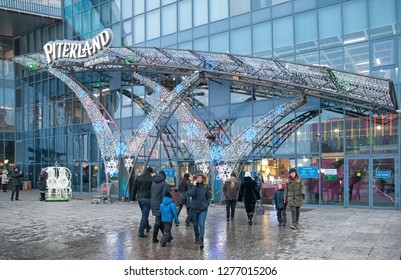 SAINT-PETERSBURG, RUSSIA – JANUARY 4, 2019: People near the enter of Piterland Shopping Mall with New Year and Christmas illumination