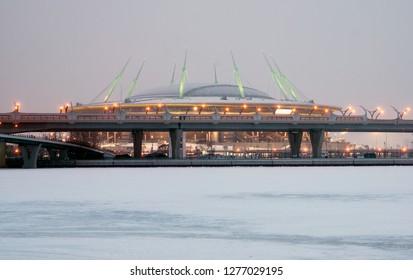 SAINT-PETERSBURG, RUSSIA – JANUARY 4, 2019: Krestovsky Stadium (Gazprom Arena) with night illumination. In the foreground is frozen Gulf of Finland