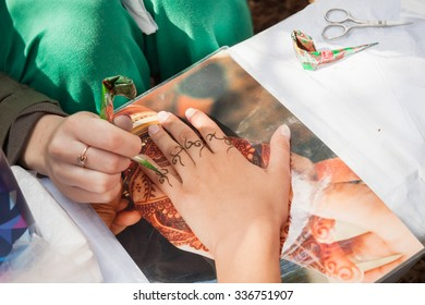 Saint-Petersburg, Russia - July 19, 2015: henna paste or mehndi application on woman hand. Traditional Indian natural skin decoration, bio-tattoo