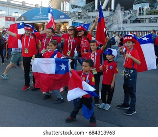 Saint-Petersburg, Russia - July 2, 2017: Joyful fans of team Chile soccer actively support their team during the Confederations Cup in Russia. Friendly family - adults and children with flags and caps