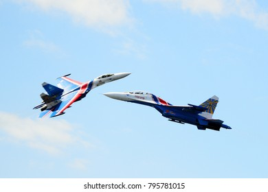 Saint-Petersburg, Russia, July 7, 2013: Two Russian Su-27 (Flanker-B) from aerobatic team Russians Knights shows imitation of air battle at port area in St. Petersburg.