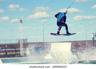 Saint-Petersburg, Russia, June 04 2016: Back view of experienced talented young rider catching air on, flying high on wakeboard, wearing swimsuit and helmet. Active healthy lifestyle and watersports
