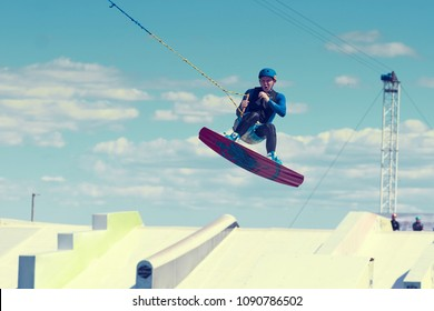 Saint-Petersburg, Russia, June 04 2016: Experienced young professional male rider demonstrating his skills during summertime watersports contest in wake park, wakeboarding, catching some air