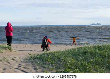 SAINT-PETERSBURG, RUSSIA - JUNE 20, 2018: A family is photographed on the shore of the Finnish bay on a windy summer day. Kronstadt