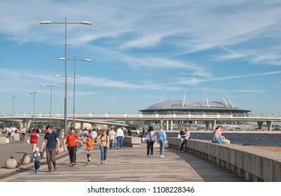 SAINT-PETERSBURG, RUSSIA – JUNE 3, 2018: People rest in 300 years St. Petersburg Anniversary Park near The Gulf of Finland. On the background is Krestovsky Stadium (Zenit Arena)
