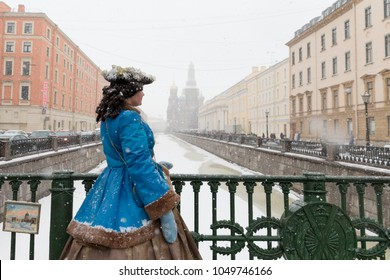 SAINT-PETERSBURG, RUSSIA - March 19, 2018 - Back view of actor in costume of Catherine II posing on bridge during a snowfall, looking aside, Church of the Savior on Spilled Blood on background