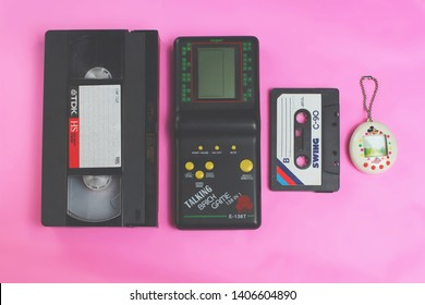 Saint-Petersburg, Russia - March 27, 2019: Old retro game tamagotchi virtual pet toy, video vhs and audio cassette tape toys  and symbols from 1990s. illustrative Editorial