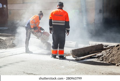 Saint-Petersburg, Russia - May 23, 2015: men at work, urban road under construction, sawing of a roadside border stones