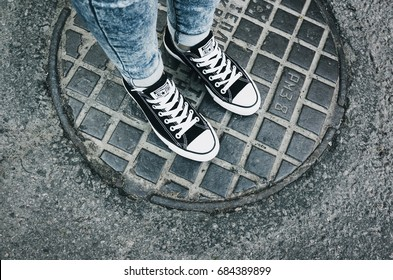 Saint-Petersburg, Russia - May 30, 2017: Teenager's feet in a pair of black canvas Chuck Taylor All-Stars casual shoes stands on urban manhole cover