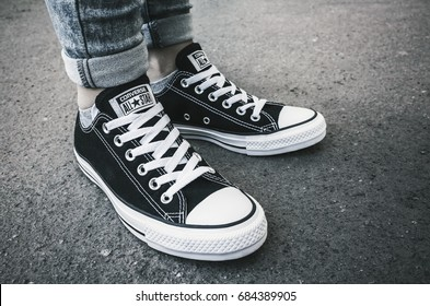 Saint-Petersburg, Russia - May 30, 2017: Teenager's feet in a pair of black canvas Chuck Taylor All-Stars casual shoes stands on urban asphalt road