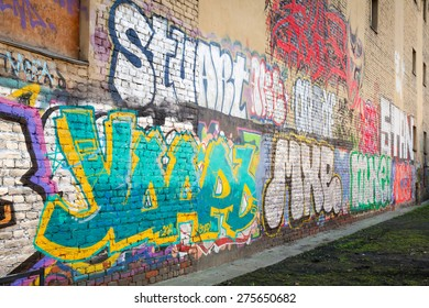 Saint-Petersburg, Russia - May 6, 2015: Abandoned urban courtyard with colorful abstract graffiti text over old damaged wall. Vasilievsky island, Central part of St. Petersburg