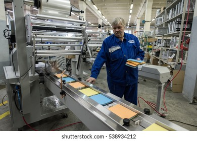 Saint-Petersburg, Russia - November 16, 2016: Engineer  conducting a test run of the machine for packaging of tissue napkins.