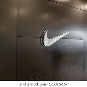 Saint-Petersburg / Russia - November 30 2018: Nike swoosh brand  white logo on a black wall in shopping center