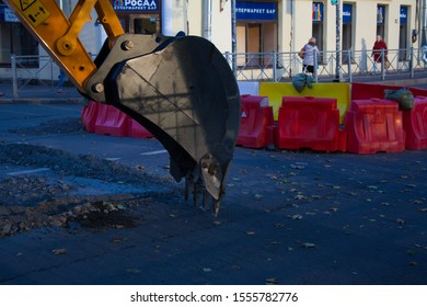 Saint-Petersburg, Russia - September 20, 2019: Bucket excavator digs a hole in the asphalt during repair work in the city center