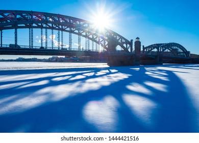 Saint-Petersburg. Russia. Winter Petersburg. Bridge over icy river. Peter the Great bridge. Bolsheokhtinsky bridge. Frozen Neva river. Petersburg bridges. Russian cities. Petersburg road architecture.