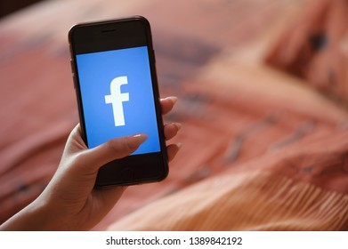 Saint-Petersburg / Russian Federation - 27 March 2019: Female hand with manicure holding cellphone with Facebook