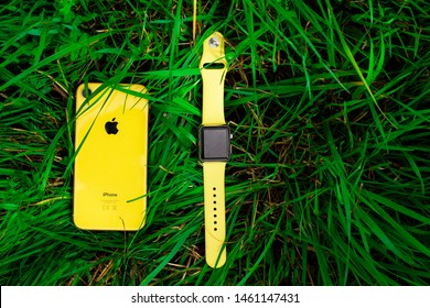 Saint-Petersburg/Russia - 07.25.2019: Yellow smartphone iPhone XR, smartwatch Apple Watch sport with the same color yellow band on the grass, green background. View from the top.