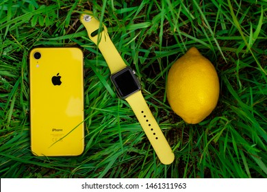 Saint-Petersburg/Russia - 07.25.2019: Yellow smartphone iPhone XR, smartwatch Apple Watch sport with the same color yellow band and a citrus fruit - lemon on the grass. View from top. Still life.