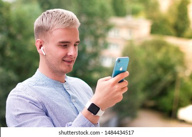 Saint-Petersburg/Russia - 08.01.2019: Handsome blonde european guy typing or texting a message on his blue iPhone XR with wireless bluetooth earphones Airpods and smartwatch Apple Watch. Apple gadgets