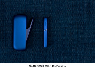 Saint-Petersburg/Russia - 09.09.2019: blue electronic cigarette by Philip Morris IQOS on dark blue background, copy space