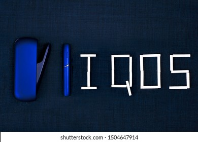 Saint-Petersburg/Russia - 09.09.2019: electronic cigarette by Philip Morris IQOS with sticks Heets on dark blue background. Tobacco heating system. Top view.