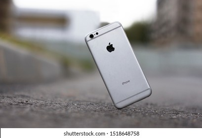 Saint-Petersburg/Russia - 09.09.2019: iPhone falling and crashes on asphalt or ground in the city, accident with smartphone. Smashed, destroyed, damaged Apple broken gadget.