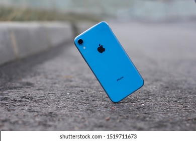 Saint-Petersburg/Russia - 09.09.2019: iPhone XR falling, crashes on asphalt, broken Apple smartphone flying down to ground. Smashed, destroyed, damaged phone. Accident with device, gadget. Crash test.