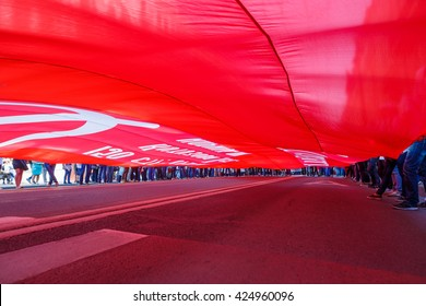 SAINT-PETERSBURG,RUSSIA - MAY 9, 2016 - Victory Day: red flags, road and legs between it.