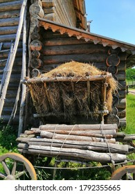 Saint-Petersburg,Russia-07.18.2020: Russian ancient village wooden buildings with a cart and firewood in the Bogoslovka Estate park ensemble in Saint-Petersburg.The church of the holy virgin