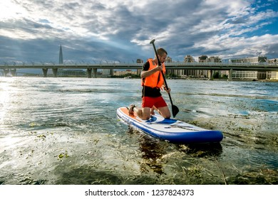 Saint-Petersburg.Russia.August 4, 2018.A man floats on the sup paddle board on the river opposite the  ring road and the skyscraper Lakhta in St. Petersburg