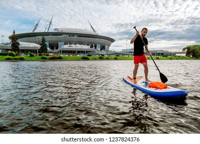 Saint-Petersburg.Russia.August 4, 2018.A man riding a sup  paddle board on the water in front of the stadium in St. Petersburg