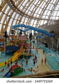 Saint-Petersburg,Russia.July,12 2019. aquapark Peterland with a transparent roof, a large wooden ship, water slides and visitors swimming in the water