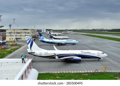 SAINT-PETERSBURG,RUSSIA-MAY 23,2015. Many airplanes (Boeings 737,Airbus A320-214 of Nordstar, Alrosa,Nordavia, Rossiya Airlines) and spotting fan in the Pulkovo International Airport