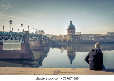 Saint-Pierre Bridge reflecting in Garonne river and Dome de la Grave with a young student in Toulouse, France