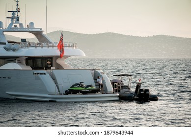 Saint-Tropez, France - July 23rd 2020: Deckhand doing morning duties on board Superyacht anchored in the Bay of Saint-Tropez, with tender and water toys on the stern