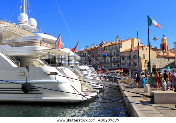 SAINT-TROPEZ, PROVENCE, FRANCE - AUGUST 21, 2016: Tourists in the old port of St Tropez, admiring the expensive luxury yachts