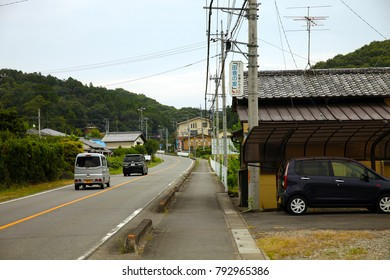 Saitama, JP - AUGUST 13, 2015: Scenery of Japan downtown street and dirty walkway in a mountain village, with two cars are running and one car is parking.