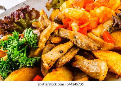 Saj with veal. Traditional Azerbaijani dish. Pieces of meat roasted with vegetables in a flat pan.