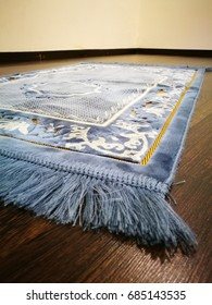 Sajadah for muslims or praying mat on wooden floor.