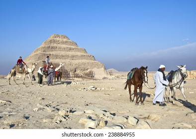 Sakaka, Egypt - January 2010: Local tour guides and tourists in the archaeological site with the stepped pyramid in the background