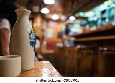 Sake bottle and cup with restaurant out of focus in the background.