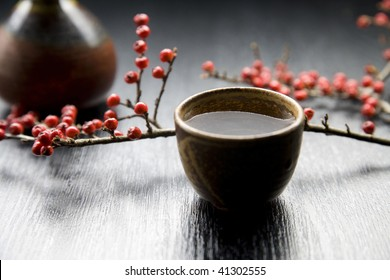 Sake in Japanese traditional cup called choko and branch of red fruits