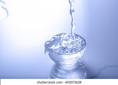 Sake pouring into overflowing glass