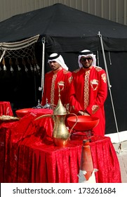SAKHIR AIRBASE, BAHRAIN - JANUARY 16: Arabic men in traditional dress serving traditional coffee Qehwa in Bahrain International Airshow at Sakhir Airbase, Bahrain on 16 January, 2014
