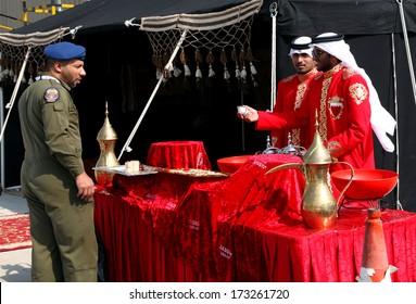 SAKHIR AIRBASE, BAHRAIN - JANUARY 16: Arabic men in traditional dress serving traditional coffee Qehwa in Bahrain International Airshow at Sakhir Airbase, Bahrain on 16 January, 2014
