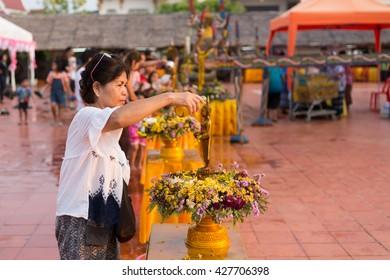 Sakon Nakhon- APRIL 15, 2016: Bathing the Buddha, A Buddhist Thai is bathing a Buddha statue to gain merit, an annual ritual for the holiday of Thai New Year on April 15, 2016, Sakon Nakhon.